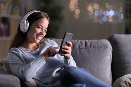 Happy woman listening to music using smart phone sitting on a couch in the night at home