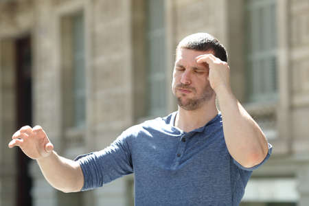 Dizzy adult man suffering headache trying to stay standing in the street
