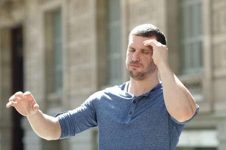 Benommener erwachsener Mann, der unter Kopfschmerzen leidet und versucht, auf der Straße stehen zu bleiben