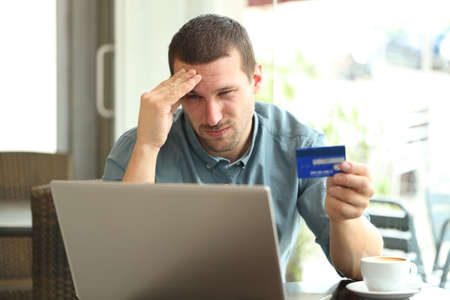Frustrated man paying with credit card and laptop sitting in a coffee shop