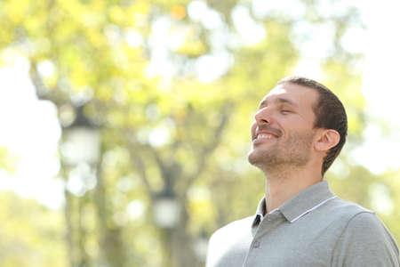 Happy casual man breathing fresh air in a park with trees in the background