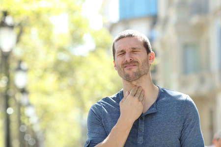 Hombre estresado que sufre dolor de garganta de pie solo en la calle Foto de archivo