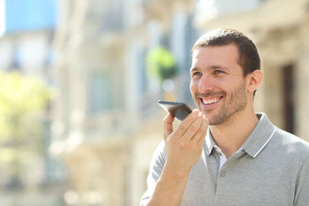 Happy man using voice recognition on mobile phone to send a recorded message in the street