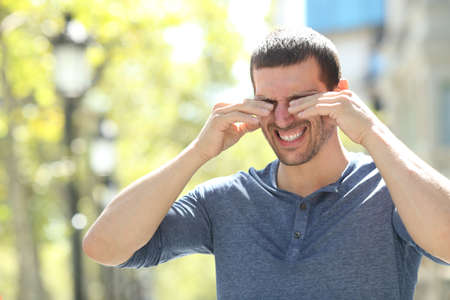 Hombre adulto rascarse los ojos con picazón con ambas manos de pie en la calle