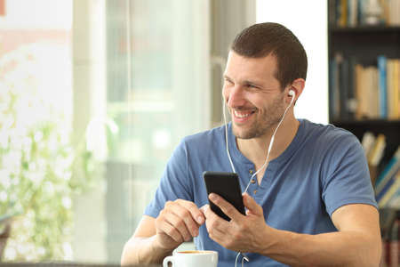 Happy man listening to music using smart phone looking outdoors through a window sitting in a bar or home