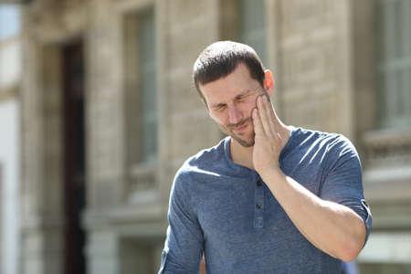 Uomo stressato che soffre di mal di denti in piedi da solo in strada