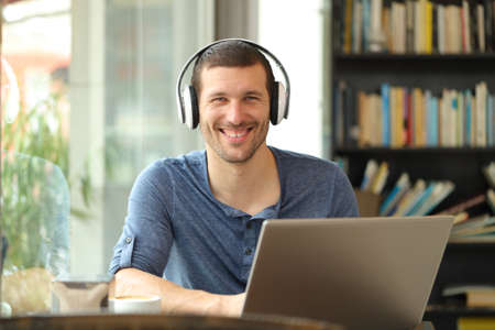 Happy man posing with headphones and laptop looking at camera sitting in a coffee shop Stok Fotoğraf