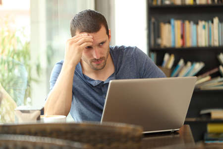 Worried adult man checking laptop online content sitting in a coffee shop