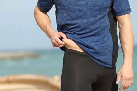 Close up of a sportsman hand pinching body fat outdoors on the beach
