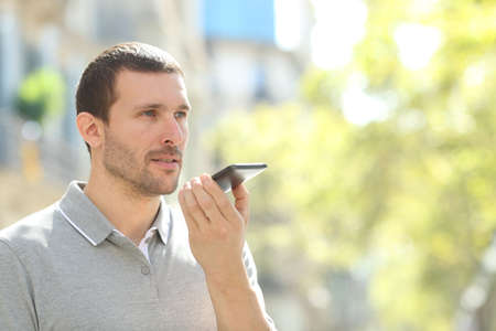 Man using voice recognition on mobile phone to record messages in the street