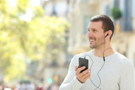 Happy adult man listening to music with earphones and phone looking at side in the street