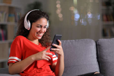 Happy girl in red listening to music checking smart phone sitting on a couch in the living room in the night at home Stok Fotoğraf