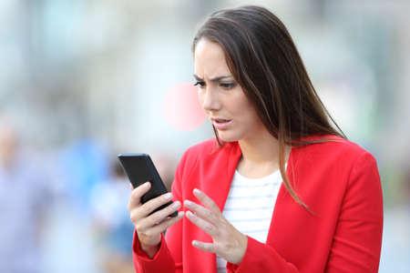 Femme inquiète en rouge lisant de mauvaises nouvelles sur un téléphone intelligent debout dans la rue