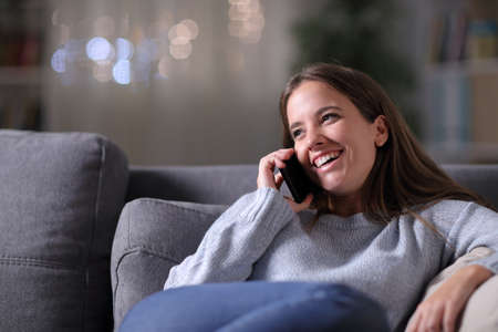 Happy woman talking on mobile phone sitting on a couch in the living room in the night at home