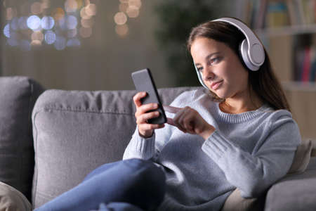 Woman listening to music using headphones and mobile phone sitting on a couch in the living room in the night at home