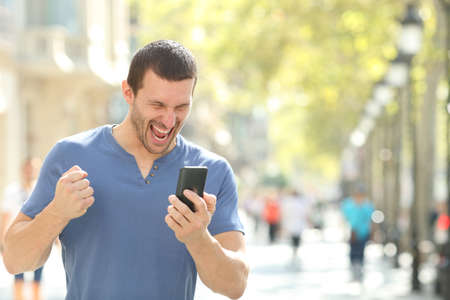 Excited man checking good news on mobile phone celebrating success in the street