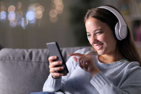 Happy woman listening to music with headphones and smartphone sitting on a couch in the living room in the night at home