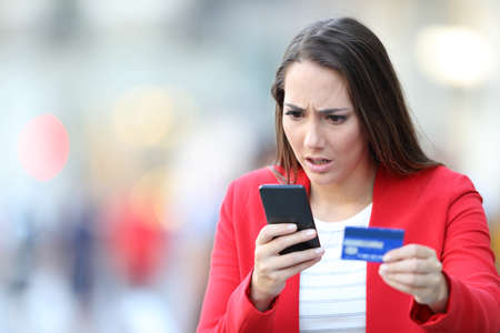 Worried woman holding credit card looking at smart phone in the street