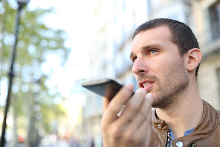 Adult man using voice recognition on mobile phone to send a recorded message in the street
