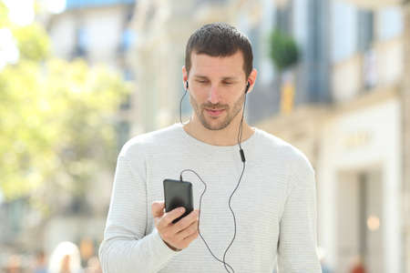 Front view portrait of a serious adult man listening to music on phone wearing earbuds in the street Stok Fotoğraf