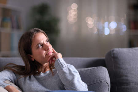 Doubtful pensive woman looking at side sitting on a couch in the living room in the night at home
