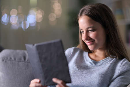 Relaxed woman reading an ebook sitting on a couch in the night at home