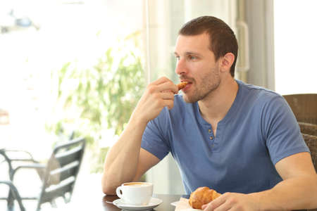 Relaxed man eating a croissant for breakfast sitting in a coffee shop