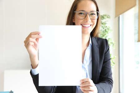 Vista frontal de una mujer de negocios feliz mostrando contrato en blanco en la oficina