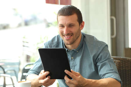 Happy man reading tablet content sitting in a coffee shop
