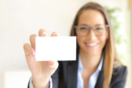 Front view of a happy businesswoman showing blank card at office