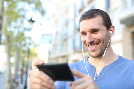 Happy adult man wearing earbuds watching videos on horizontal mobile phone in the street Stock Photo