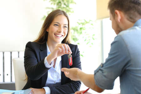 Realtor giving house keys to a client after closing deal at office