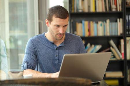 Ernster Mann, der einen Laptop verwendet, um Daten einzugeben, die in einem Café oder zu Hause sitzen?