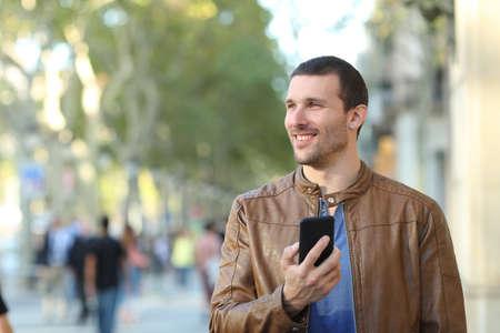 Vue de face portrait d'un homme heureux tenant un téléphone intelligent marchant vers la caméra en regardant de côté dans la rue