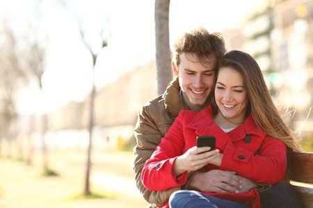 Feliz pareja navegando por el contenido de un teléfono inteligente sentado en un banco en la calle en invierno Foto de archivo