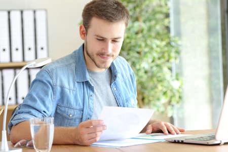 Empresario satisfecho trabajando leyendo un documento en papel sentado en una silla en la oficina
