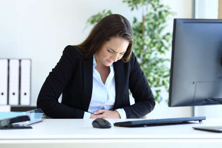 Young businesswoman suffering bellyache working sitting at office