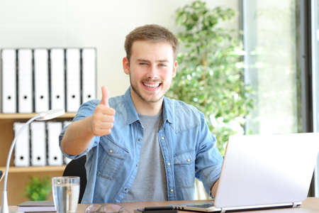Front view portrait of a happy entrepreneur gesturing thumbs up at office