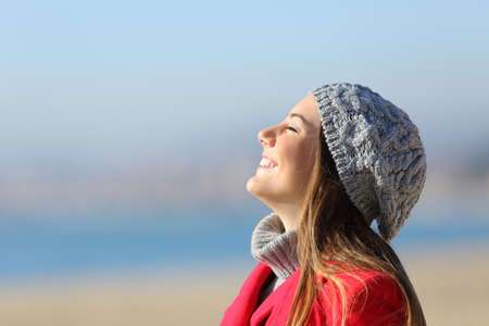 Happy woman breathing deeply fresh air celebrating new day standing on the beach in winter Standard-Bild