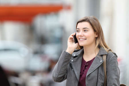 Happy casual girl talking on mobile phone walking in the street