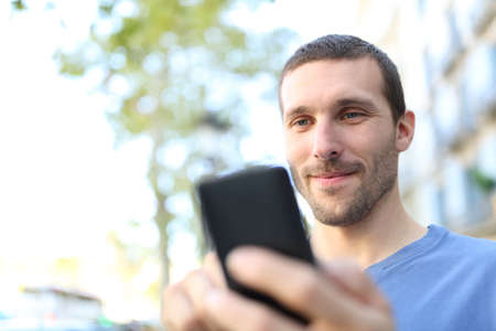 Close up of a satisfied man using smart phone walking in the street