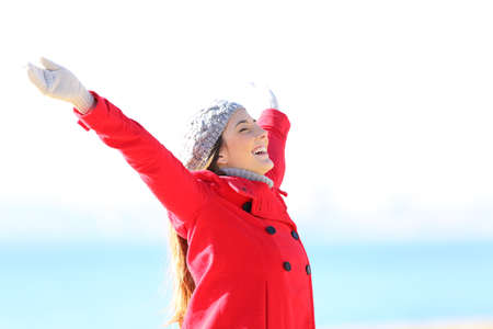 Excited woman in red raising arms celebrating winter standing on the beach