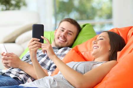 Happy couple lying on colorful poufs at home sharing mobile phone content Stock fotó