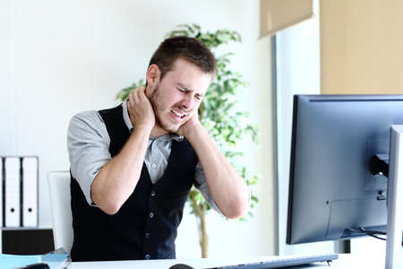 Young executive man suffering neck ache working sitting at office