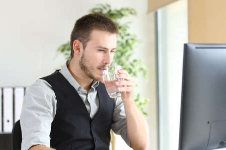 Businessman working drinking water with a glass at office