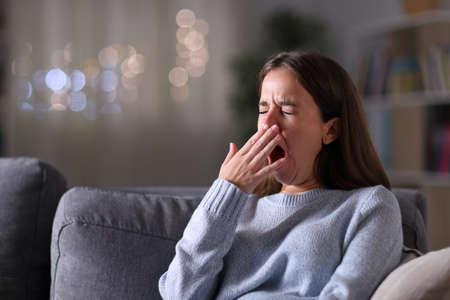 Femme fatiguée bâillant couvrant la bouche avec une main assise sur un canapé dans la nuit à la maison