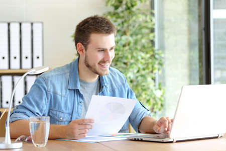 Casual happy entrepreneur working using laptop holding document comparing data at office