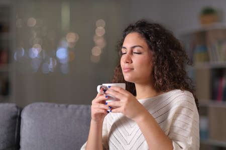 Relaxed woman smelling coffee cup sitting on a couch in the night at home