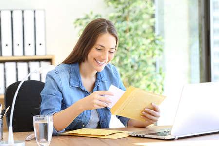 Gelukkige ondernemer die document in een envelop stopt die op kantoor werkt Stockfoto