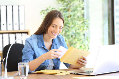 Happy entrepreneur putting document in an envelope working at office Stock Photo